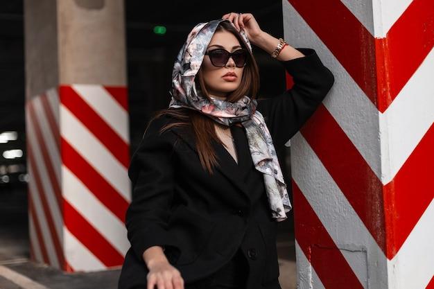 Elegante giovane donna professionale in elegante sciarpa di seta sulla testa in occhiali da sole alla moda in cappotto vintage nero in posa vicino alla colonna rosso-bianca sulla strada. ragazza europea alla moda in città. signora di bellezza