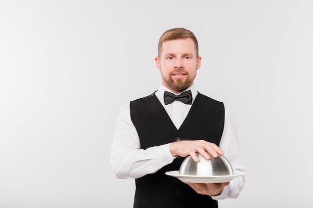 Elegante giovane cameriere in papillon e panciotto nero che tiene cloche con cibo per uno dei clienti del ristorante