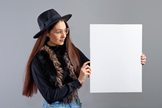 Elegante giovane donna in occhiali e cappello che mostra banner di bordo vuoto, isolato su grigio, copia spazio