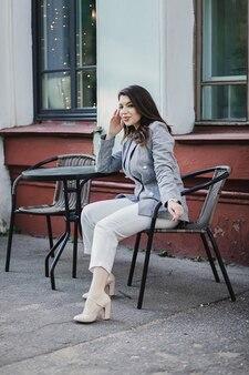 Elegante giovane donna in giacca in posa in caffè e sorriso della città