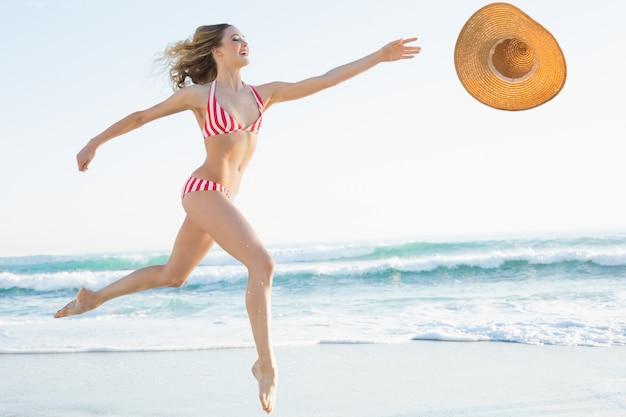 Elegante giovane donna che salta sulla spiaggia