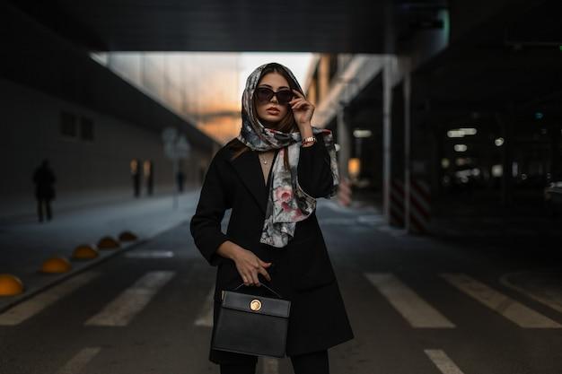 Elegante giovane donna in scialle di seta sulla testa in cappotto nero elegante con borsa in pelle alla moda raddrizza occhiali da sole vintage in strada. la bella ragazza professionale sta sulla strada vicino al parcheggio.