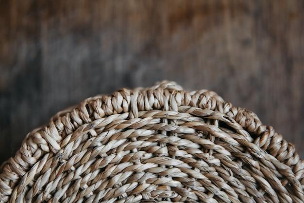 Elemento di un cesto di vimini rotondo su uno sfondo di legno modello di struttura rotonda