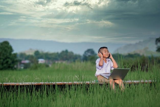 Bambino della scuola elementare che utilizza il computer portatile