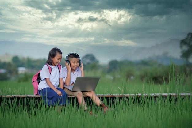Bambini delle scuole elementari con una maschera utilizzando il laptop
