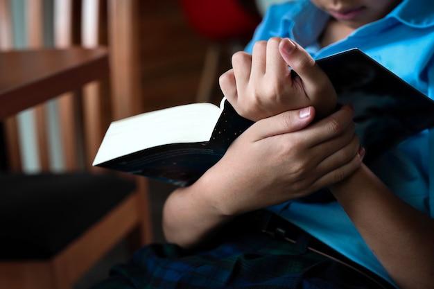 Il ragazzo della scuola elementare legge e tiene il bigbook in mano.
