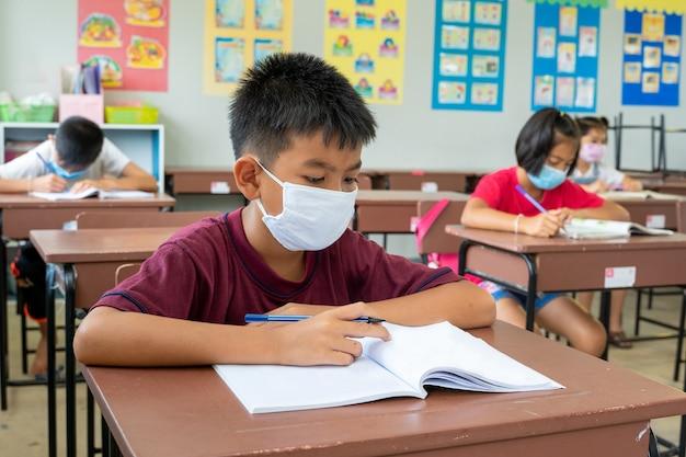 I bambini delle scuole elementari indossano una maschera per proteggere il virus corona