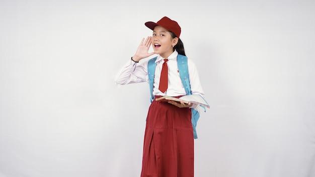 Bambina della scuola elementare che grida al lato isolato su fondo bianco