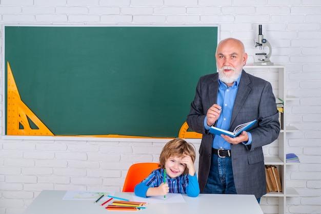 Insegnante senior di scuola elementare con allievo in fondo all'aula della scuola elementare