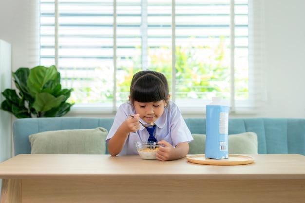 Ragazza studentessa delle scuole elementari in uniforme che mangia cereali per la colazione con latte nella routine scolastica mattutina