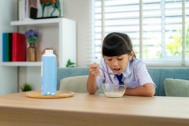 Ragazza studentessa di scuola elementare in uniforme che mangia cereali per la colazione con latte al mattino