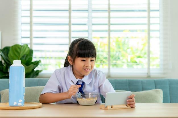Ragazza studentessa delle scuole elementari in uniforme che mangia cereali per la colazione con latte