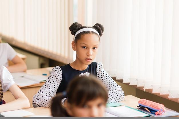 Scolari elementari che scrivono nei libri nell'aula