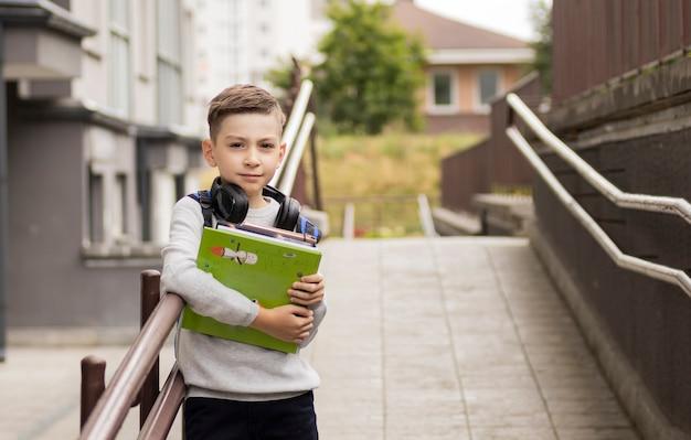 Studente elementare davanti a casa sua sorridente con zaino