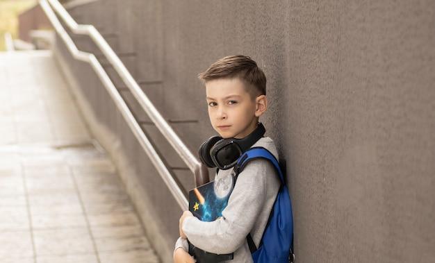 Studente elementare davanti a casa sua sorridente con zaino Foto Premium