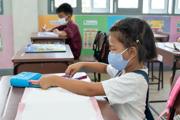 Studente delle elementari con maschera facciale a scuola dopo il blocco della quarantena covid-19