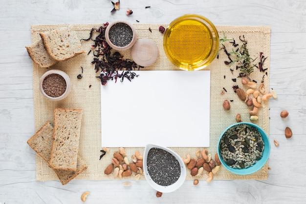 Vista elevata di carta bianca circondata da cibo sano sopra tovaglietta sul tavolo