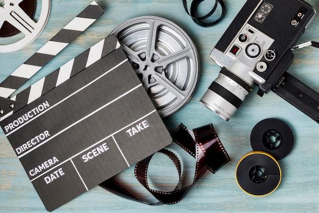 Una vista elevata di ciak; bobine di film; strisce di pellicola e videocamera su sfondo blu in legno