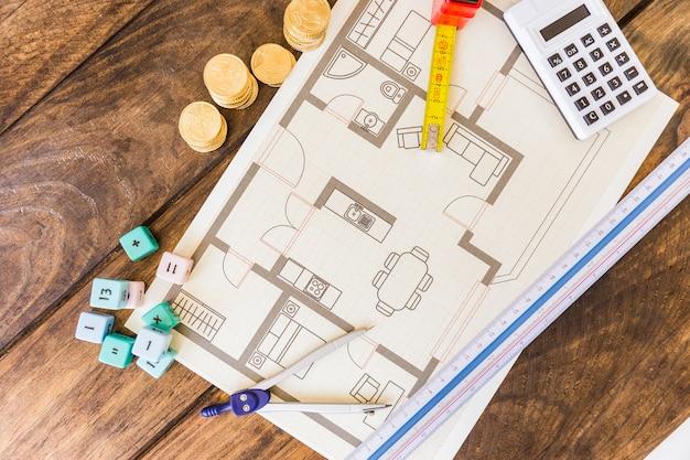 Vista elevata del divisore, del righello, dei blocchi per la matematica, del calcolatore, delle monete impilate e del modello su fondo di legno
