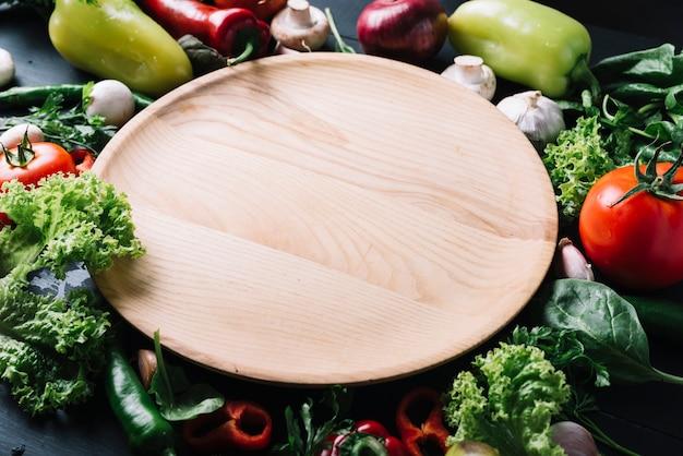 Vista elevata del vassoio di legno circondato da verdure crude