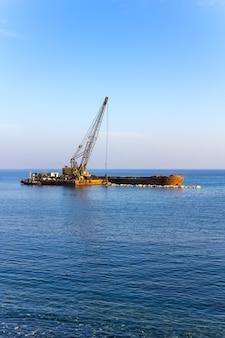 La gru elevatrice scarica le pietre dalla chiatta in mare