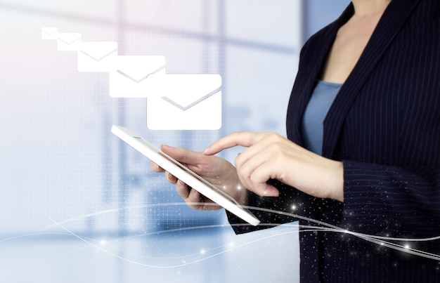 Concetto di e-mail marketing. invio newsletter. compressa bianca di tocco della mano con l'ologramma digitale email e sms firmano su fondo vago leggero. invio di posta elettronica.posta in blocco.