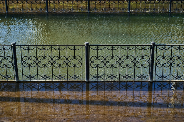 L'argine di un canale cittadino con ringhiere metalliche sopra l'acqua viene allagato durante l'alluvione primaverile