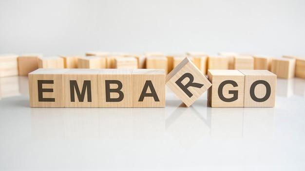 Embargo - parola di blocchi di legno con lettere su sfondo grigio. riflessione della didascalia sulla superficie specchiata del tavolo. messa a fuoco selettiva.