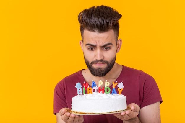 Imbarazzato giovane maschio hipster con la barba che tiene una torta di compleanno nelle sue mani e alla ricerca