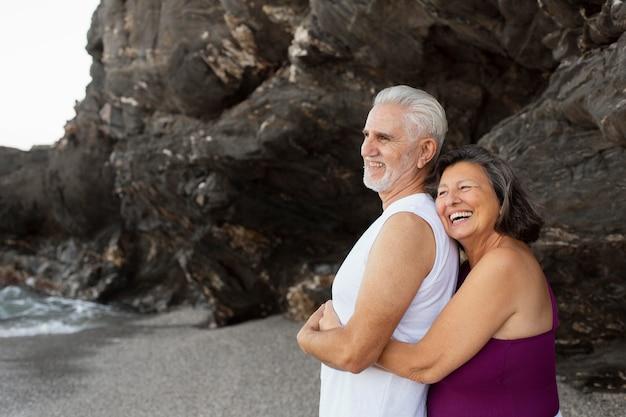 Coppia senior abbracciata che si gode la giornata in spiaggia