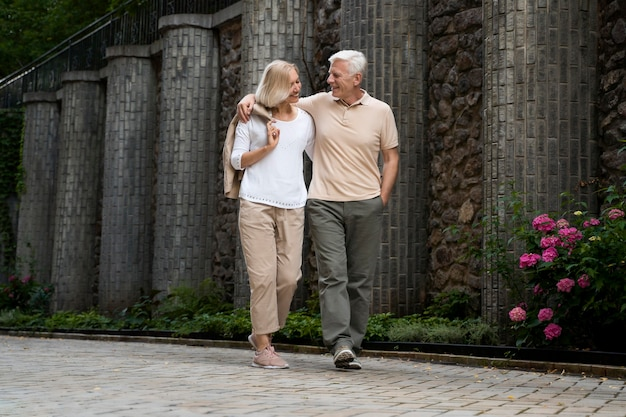 Coppia senior abbracciata facendo una passeggiata all'aperto