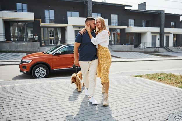 Abbracciandosi l'un l'altro. una coppia adorabile fa una passeggiata insieme al cane all'aperto vicino alla macchina.