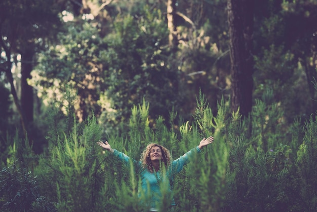 Abbracciando il concetto di natura all'aperto e amore con una bella donna felice nel mezzo di un bosco di alberi forestali in totale felicità e gioia