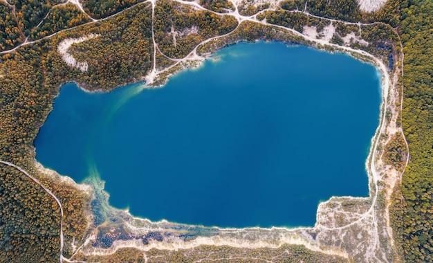 Lago smeraldo in una cava allagata nella foresta, vista aerea