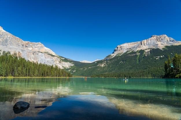 Lago di smeraldo in estate con foreste e montagne alle spalle