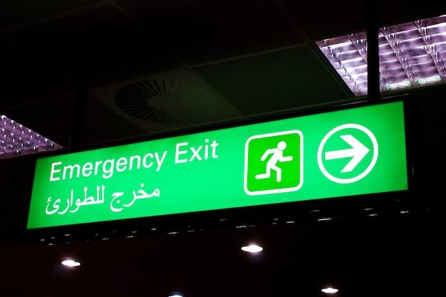 Segnale di uscita di emergenza in un aeroporto internazionale in medio oriente con informazioni in arabo