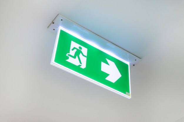 Porta di uscita d'emergenza dal fuoco. porta di uscita dal soffitto. segno verde dell'uscita di sicurezza che mostra il modo.