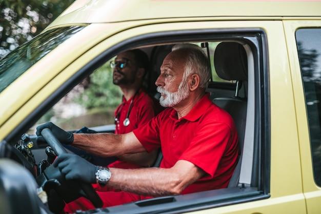 Operai di sesso maschile del servizio medico di emergenza che guidano in auto ambulanza.