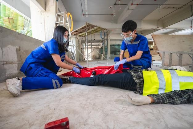 Squadre mediche di emergenza stanno aiutando un operaio edile con un incidente a una gamba rotta in un cantiere edile. il team di sicurezza aiuta l'incidente dei dipendenti.