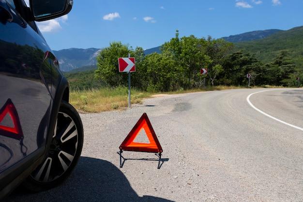 Un segnale di arresto di emergenza di un veicolo è installato sulla strada, accanto all'auto. copia spazio.