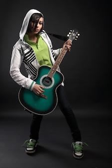 Ragazza emo con la chitarra su sfondo nero