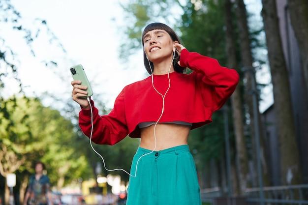 Emotinal donna ascoltando musica per strada, carina donna millenaria in maglione rosso alla moda avendo utilizzando gli auricolari e ascoltare musica
