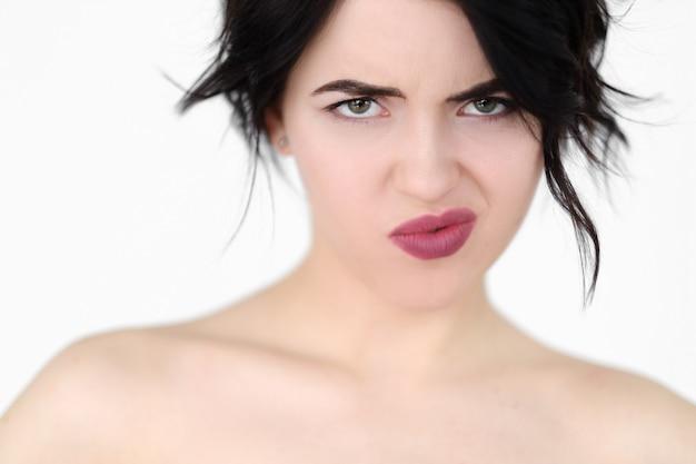 Emozione di fronte alla mancanza di rispetto. donna scontenta scontenta infastidita sul muro bianco.
