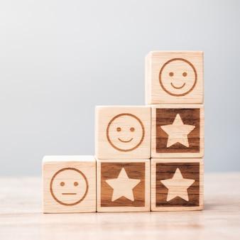 Blocchi di simbolo faccia e stella emozione sullo sfondo della tabella. valutazione del servizio, classifica, recensione del cliente, soddisfazione, valutazione e concetto di feedback