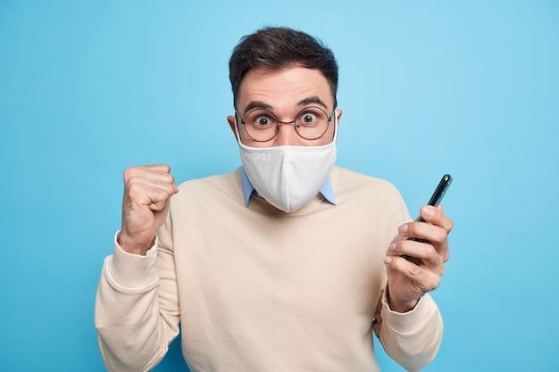 L'uomo adulto emotivo stringe il pugno sembra eccitato, indossa una maschera per prevenire la diffusione del coronavirus tiene il cellulare vestito con un maglione