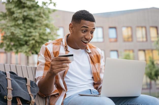 Uomo afroamericano emotivo con carta di credito che fa acquisti online con grandi vendite il black friday