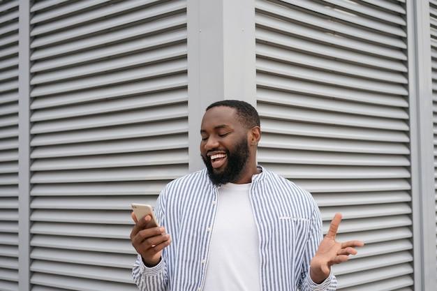 Emotivo uomo afroamericano utilizzando il telefono cellulare, comunicazione in piedi sulla strada