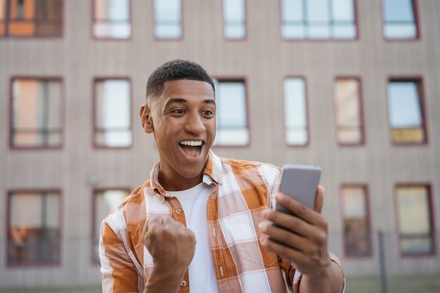 Uomo afroamericano emotivo che utilizza il telefono cellulare per lo shopping online happy guy celebrazione successo