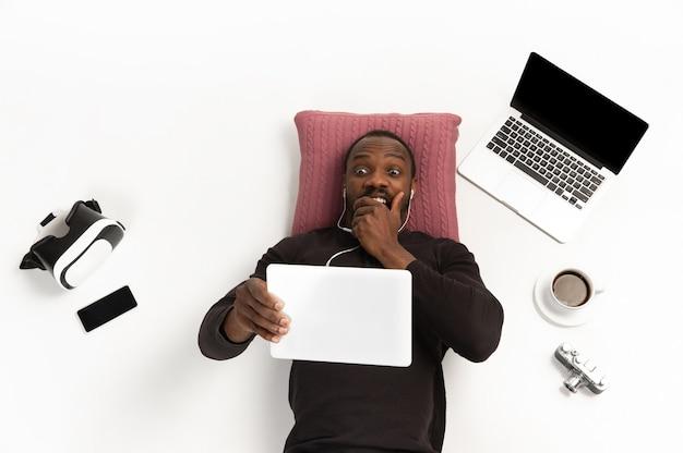 Uomo afroamericano emotivo che utilizza tablet circondato da gadget isolati sulla parete bianca dello studio.