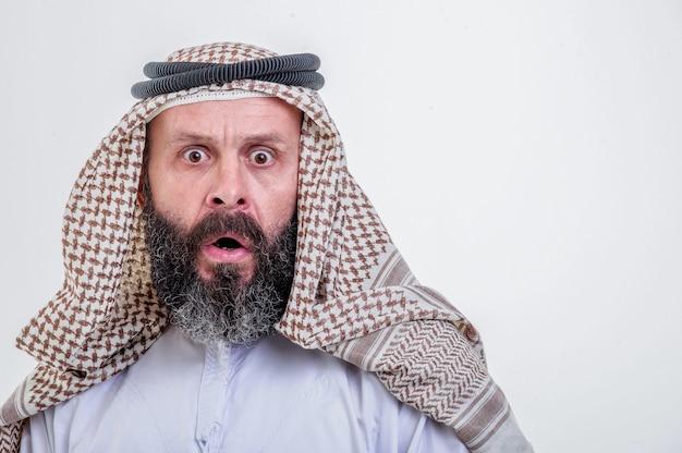 Uomo arabo emotivo in posa su sfondo bianco.